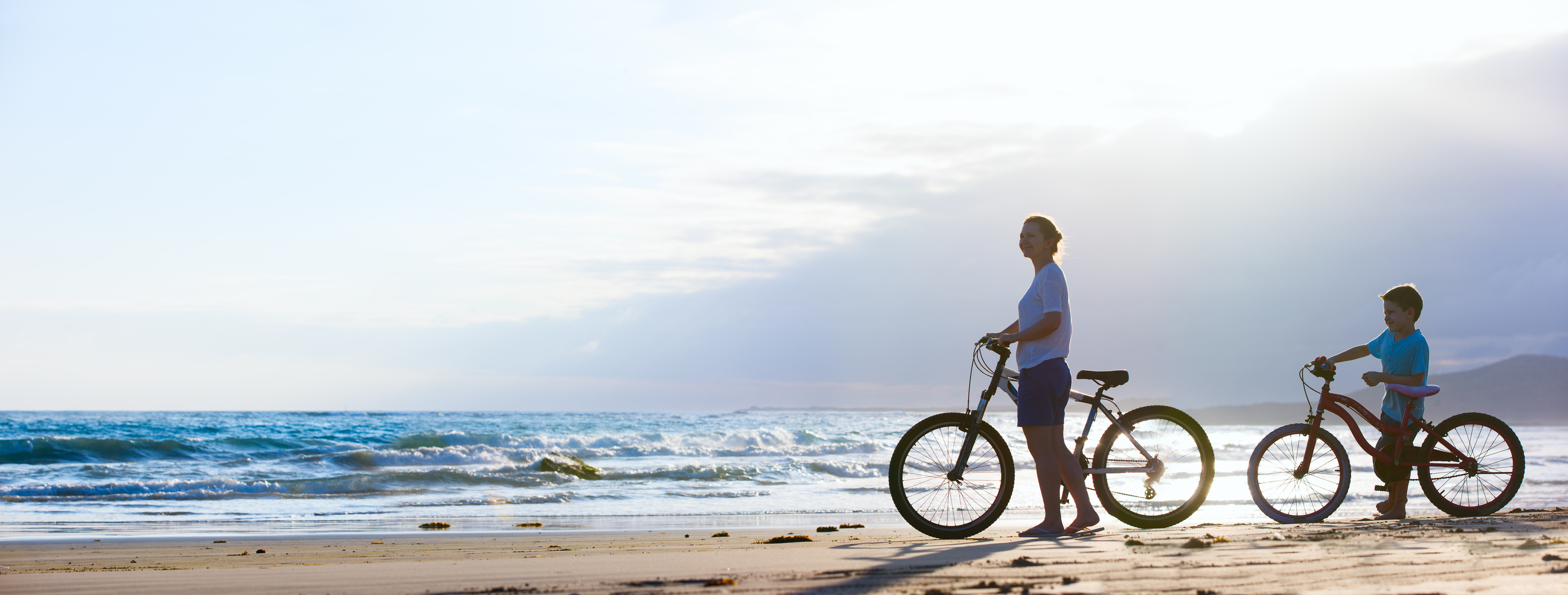 Mother and son biking at beach